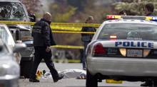 Police examine a dead body near Ross and 61st Avenue after what police say was a drive-by shooting in Vancouver, British Columbia on May 2, 2012. The shooting was a block away from Moberly Elementary School. (Ben Nelms for The Globe and Mail)