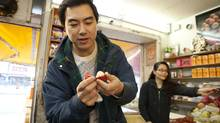 Film maker and director Yung Chang open a rambutan fruit at K&K Specialty Tropical Fruit market on Spadina Avenue in Toronto on Nov. 9, 2012 while talking about fruit and his new film The Fruit Hunters. (Deborah Baic/The Globe and Mail)