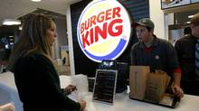 "Burger King is in talks to buy Tim Hortons, in hopes of creating a Canadian holding company, bound by Canadian ""territorial"" tax laws and rates which are generally lower than in the U.S. (Claude Paris/AP Photo)"