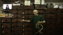 Snake shop owner Mak Tai-kong, 84, holds snakes which were caught in mainland China, in front of wooden cabinets containing snakes, at his snake soup store in Hong Kong January 29, 2013. (Bobby Yip/Reuters)
