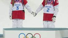 Sisters Justine, left, and Chloé Dufour-Lapointe of Canada hold hands before climbing onto the podium after winning the gold and silver medals in the moguls at the Sochi Winter Olympics on Feb. 8, 2014. (Adrian Wyld/The Canadian Press)