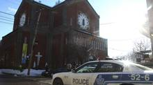 A police car sits outside the church during the funeral of mob boss Vito Rizzuto in Montreal December 30, 2013. Rizzuto died of natural causes in a hospital on December 23, 2013. Ducarme Joseph, a 46-year-old once described by police as the city's most dangerous street gang leader, died in the middle of the road just metres from his mother's home in the rough-and-tumble neighbourhood of St-Michel last Friday night. Mr. Joseph was believed to be linked to the 2009 shooting of Vito Rizzuto's son, Nicolo Rizzuto. (Christinne Muschi For The Globe and Mail)