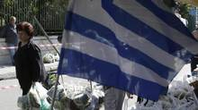 People holding shopping bags full of fruits and vegetables pass a Greek flag during a protest by farmers' market vendors in the Athens' suburb of Gerakas on May 5, 2014. (THANASSIS STAVRAKIS/ASSOCIATED PRESS)
