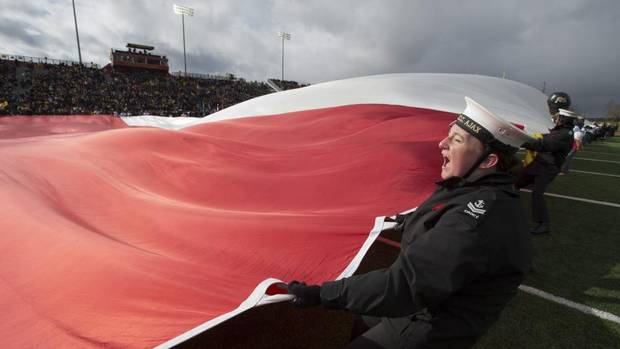 Cadets struggle with a large Canadian flag in high winds during pre-game ceremonies before East Division semifinal CFL action between the Hamilton Tiger-Cats and the Montreal Alouettes in Guelph, Ont., on Sunday, Nov. 10, 2013. (FRANK GUNN/THE CANADIAN PRESS)