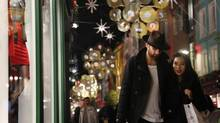 A couple walk past a shop window in London Nov. 13, 2012. (LUKE MACGREGOR/Reuters)