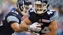 Toronto Argonauts quarterback Ricky Ray (19) hands off the ball to running back Chad Kackert (44) during first quarter CFL action against the Saskatchewan Roughriders in Toronto on Thursday July 11, 2013. (Frank Gunn/THE CANADIAN PRESS)