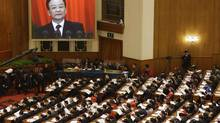 China's Premier Wen Jiabao (shown on screen) speaks as delegates listen during the opening ceremony of National People's Congress (NPC) at the Great Hall of the People in Beijing, March 5, 2013. (JASON LEE/REUTERS)