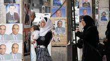 Syrians walk past posters of paramilitary candidates for the upcoming elections in Damascus, May 1, 2012 (Bassem Tellawi/AP/Bassem Tellawi/AP)