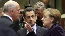 In this Friday, Feb. 9, 2011 file photo, German Chancellor Angela Merkel, right, speaks with Greek Prime Minister George Papandreou, left, and French President Nicolas Sarkozy during a round table meeting at an EU summit in Brussels. During a G20 meeting in Cannes, France on Wednesday, Nov. 2, 2011, French President Nicolas Sarkozy will hold emergency talks with European leaders. (Yves Logghe/The Associated Press)