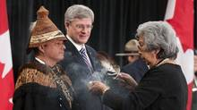 A native elder performs a smudging ceremony with Shawn Atleo, national chief of the Assembly of First Nations, and Prime Minister Stephen Harper at the opening of the Crown-First Nations Gathering in Ottawa in January. (Adrian Wyld/The Canadian Press)