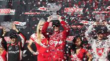 Scott Dixon, of New Zealand, centre, celebrates with second place finisher Helio Castroneves, of Brazil, left, and third place finisher Sebastien Bourdais, of France, after the Toronto Indy race in Toronto on Sunday, July 14, 2013. (CP)