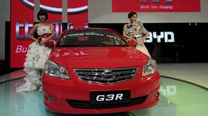 Models pose next to a G3R, a car by Chinese automaker BYD Auto, at the Guangzhou Autoshow on Dec. 20, 2010.