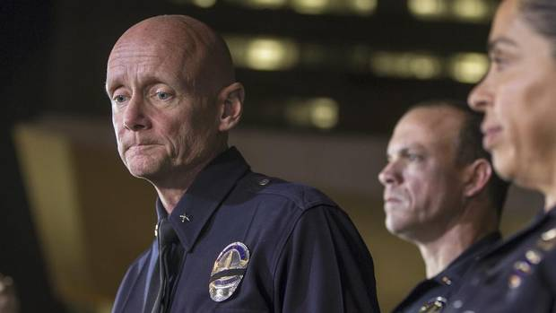 Los Angeles Police Commander Andrew Smith, left, expresses condolences for the death of a San Bernardino County deputy as he briefed reporters on the shootout scene in Big Bear involving triple-murder suspect Christopher Jordan Dorner during a late news conference in Los Angeles on Feb. 12, 2013. (Damian Dovarganes/AP)