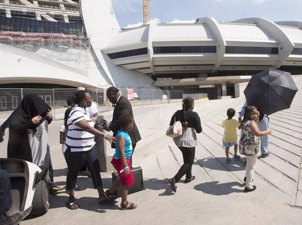 A group of asylum seekers leave Olympic Stadium, which has been set up as a temporary shelter.