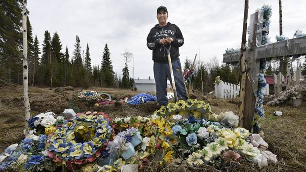 Fraser Meekis stands by the grave of his son Brody on the Sandy Lake First Nation reserve in Northern Ontario.