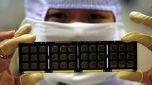 A woman displays semiconductors at the Infineon Technologies plant in this file photo. (SIMON THONG/Associated Press)