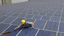 A worker cleans solar panels on the rooftop of the Yiwu International Trade City in Yiwu, Zhejiang province May 20, 2011. Japan?s Prime Minister Naoto Kan is expected to announce a drive towards renewable energy, including slashing the cost of solar power, when he meets fellow leaders of the G8 rich nations group later this week, media reports say. (CHINA DAILY/REUTERS)