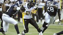 Hamilton Tiger-Cats running back Terry Grant (C) breaks a tackle by Toronto Argonauts defenders Willie Pile (L) and Byron Parker (R) during the second half of their CFL football game in Toronto October 1, 2011. (MIKE CASSESE/REUTERS)