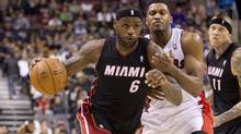 LeBron James drives past Rudy Gay during NBA action between the Toronto Raptors and the Miami Heat at the ACC in Toronto on Nov. 5, 2013. (Peter Power/The Globe and Mail)
