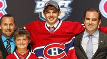 Alex Galchenyuk, center, smiles with officials from the Montreal Canadiens after being chosen third overall in the first round of the NHL hockey draft on Friday, June 22, 2012, in Pittsburgh. (Associated Press)