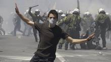 A protester runs as others are caught by riot police during clashes in Athens, Wednesday, May 11, 2011 (Petros Giannakouris/Petros Giannakouris/The Associated Press)