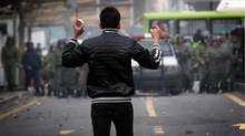 An Iranian opposition protester holds stones as he stands opposite security forces during clashes in Tehran on Sunday. (-/AFP/Getty Images)