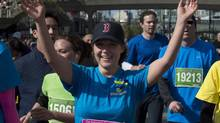 B.C. Liberal Leader Christy Clark crosses the finish line after finishing the Vancouver Sun Run on April 21, 2013. She wore a Boston Red Sox cap in solidarity with the city recently hit by bombs during its historic marathon. (JONATHAN HAYWARD/THE CANADIAN PRESS)