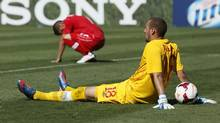 Canada goalkeper Milan Borjan (R) and his teammate Russell Teibert react after Martinique's Fabrice Reuperne scored a goal during extra time in the second half of their CONCACAF Gold Cup soccer game in Pasadena, California, July 7, 2013. (DANNY MOLOSHOK/REUTERS)