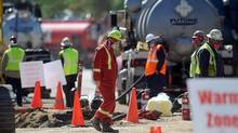 Enbridge workers clean up the oil spill in Romeoville, Ill., (Michael R. Schmidt)