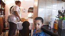 Anastasia Thomas sets out cereal while son Ethan, 5, waits to eat. The civil servant is up by 5:30 a.m. to make sure her kids get their baths and breakfast. (Erin Conway-Smith for The Globe and Mail)