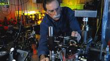 "In this 2003 photo provided by Geoffrey Wheeler and the National Institute of Standards and Technology, physicist David Wineland adjusts an ultraviolet laser beam used to manipulate ions in a high-vacuum apparatus containing an ""ion trap"" used to demonstrate the basic operations required for a quantum computer. Wineland and Serge Haroche of France shared the 2012 Nobel Prize in physics Tuesday, Oct. 9, 2012 for inventing methods to observe the bizarre properties of the quantum world, research that has led to the construction of extremely precise clocks and helped scientists take the first steps toward building superfast computers. (Geoffrey Wheeler/AP)"