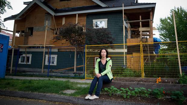 Eveline Xia sits for a photograph near a house being renovated in the community where she lives in East Vancouver, B.C., on Monday May 25, 2015.
