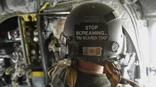 A Canadian crewman stands inside a CH-47 Chinook helicopter flying over Kandahar province in southern Afghanistan, July 5, 2011. Canada is winding up combat operations in Afghanistan and all combat troops will leave by the end of July, after nearly ten years fighting in Afghanistan. (BAZ RATNER/REUTERS)