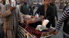 People care for a person injured in a blast on Monday, Dec. 3, 2012 in Peshawar, Pakistan. A bomb ripped through a police van as it was patrolling in northwestern Pakistan on Monday, killing several officers and wounding others, police said. (Mohammad Sajjad/AP)