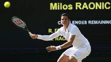 Milos Raonic of Canada plays a return to Roger Federer of Switzerland during their men's singles semifinal match at the All England Lawn Tennis Championships in Wimbledon, London, Friday, July 4, 2014. (Associated Press)