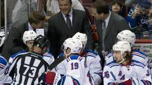 New York Rangers head coach Alain Vigneault, centre, laughs during the first period of NHL pre-season hockey action against the Vancouver Canucks in Vancouver on Thursday, Sept 26, 2013. (JONATHAN HAYWARD/THE CANADIAN PRESS)