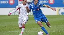 Montreal Impact's Davy Arnaud (22) challenges New England Revolution's Diego Fagundez for the ball during first half MLS action in Montreal, Saturday, October 27, 2012. (Graham Hughes/THE CANADIAN PRESS)