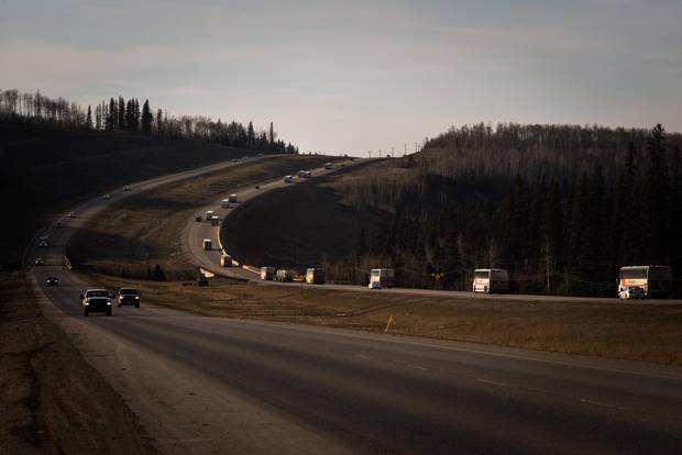 FORT MCMURRAY, AB -- MAY 7, 2015: A string of Diversified coach busses head north on highway 63, to to pick up workers Syncrude during the Thursday evening shift change, north of Fort McMurray, Alberta, May 7th, 2015. (Ian Willms for the Globe and Mail)