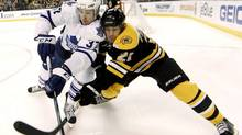 Boston Bruins' Andrew Ferrance, right, battles for position with Toronto Maple Leafs' Carter Ashton during the first period of an NHL game in Boston, Monday, March 19, 2012. (Winslow Townson/AP)