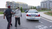 A man under arrest is brought to a scout car on Western Battery Road. Police arrested 50 people allegedly linked to two rival gangs in pre-dawn raids throughout Toronto on Wednesday, including in high-end downtown condos.