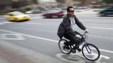 A cyclist rides in the bike lanes on Jarvis Street in Toronto. (Kevin Van Paassen/The Globe and Mail)