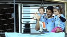 Uruguay's soccer player Luis Suarez, with his children Benjamin, left, and Delfina, waves to fans from his home, before the start of his team's World Cup round 16 match with Colombia, on the outskirts of Montevideo, Uruguay, Saturday, June 28, 2014. (Matilde Campodonico/AP)