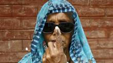 A woman shows her ink-marked finger after casting her vote at Makum village in Tinsukia district in the northeastern Indian state of Assam April 7, 2014. (RUPAK DE CHOWDHURI/REUTERS)