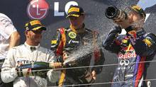 Mercedes Formula One driver Lewis Hamilton (L) of Britain sprays champagne on third place winner Red Bull Formula One driver Sebastian Vettel (R) of Germany as second-placed Lotus F1 Formula One driver Kimi Raikkonen (C) of Finland looks on, on the podium at the Hungarian F1 Grand Prix at the Hungaroring circuit in Mogyorod, near Budapest July 28, 2013. (BERNADETT SZABO/REUTERS)