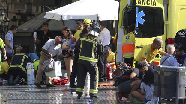 Injured people are treated in Barcelona, Spain, on Aug. 17, 2017, after a white van jumped the sidewalk in the historic Las Ramblas district.