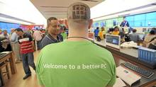 Employee Nathan Castaldi, who shaved his head with the Microsoft logo, helps a customer inside the new Microsoft Store at Lenox Square in Atlanta, Georgia, May 27, 2011. (ERIK S. LESSER)