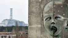 A graffiti is pictured on a wall in the ghost city of Pripyat near the fourth nuclear reactor (background) at the former Chernobyl Nuclear power plant, site of the world's worst nuclear disaster, on April 4, 2011. (SERGEI SUPINSKY/SERGEI SUPINSKY/AFP/Getty Images)