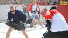 Canadian (right) and American troops face off in a ball hockey game at the military base in Kandahar, Afghanistan, Sunday, Feb.21, 2010.The game's organizers billed it as Hockey Night in Kandahar - never mind that the teams played under the blazing mid-afternoon Afghan sun - and for a couple of hours, players and fans forgot a war is raging outside the walls of this sprawling military base. (Steve Rennie/THE CANADIAN PRESS/Steve Rennis)