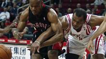 Houston Rockets forward Chuck Hayes, right, and Toronto Raptors guard Jarrett Jack, left, get tangled up as they struggle for a loose ball during the first half of their NBA basketball game in Houston March 1, 2010. (RICHARD CARSON)