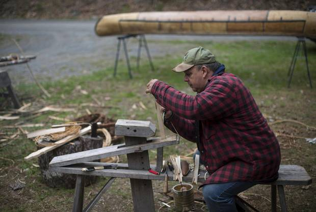 Todd Labrador straddles the draw horse while shaving wooden pegs to hold the canoe's gunwale cap in place.